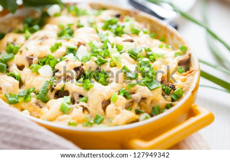 gratin with parmesan and mushrooms in a yellow dish, closeup