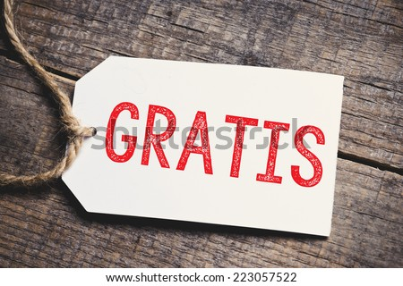 Gratis on blank tags. Red inscription Gratis on blank tags on wooden table  - stock photo