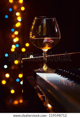 Gratitude for the maestro, snifter with brandy on a piano. - stock photo