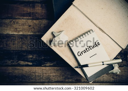 Gratitude word on pages sketch book on wood table vertical  - stock photo