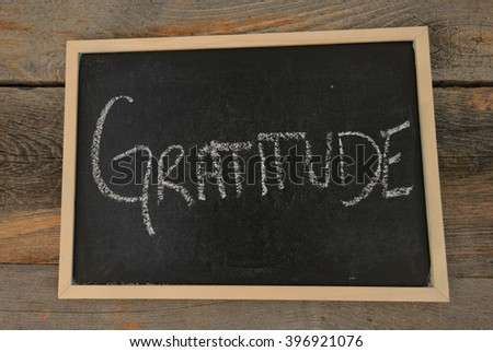 Gratitude written in chalk on a chalkboard on a rustic background - stock photo