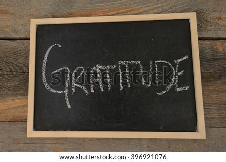 Gratitude written in chalk on a chalkboard on a rustic background - stock photo