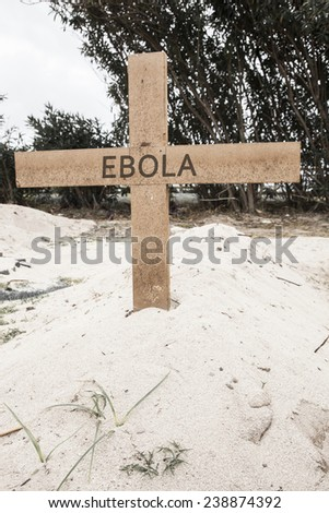 Grave in the desert sand. On a wooden cross is written the word EBOLA. Concept for danger caused by EBOLA virus. - stock photo