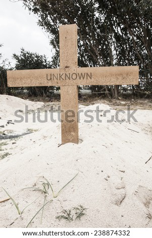 Grave in the desert sand. On a wooden cross is written the word unknown. Concept for death of an unknown person or soldier, died in war. - stock photo
