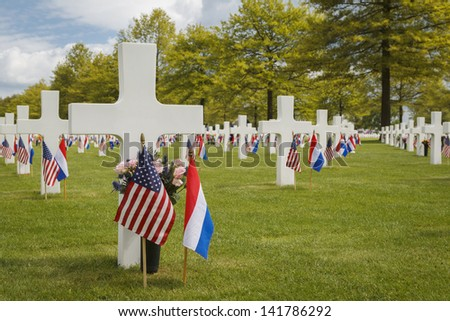 Grave markers at the American War Cemetery of Margraten in the Netherlands, decorated with flags for Memorial Day.  - stock photo