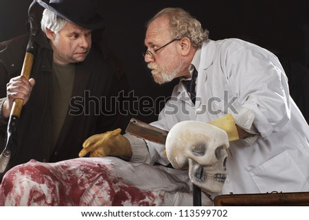 Grave robber and evil doctor with bloody cleaver exchange conspiratorial glances. Stage effect, isolated on black background, spot lighting. - stock photo