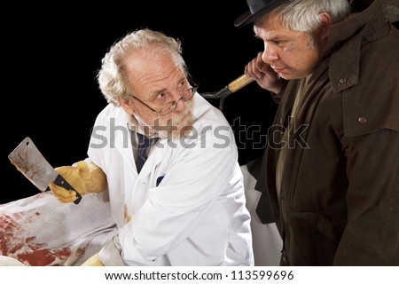 Grave robber and evil doctor with bloody cleaver exchange glances. Stage effect, isolated on black background, spot lighting. - stock photo