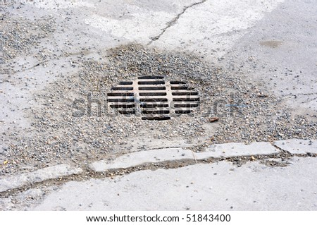 Gravel covered Storm Drain in an urban roadway - stock photo