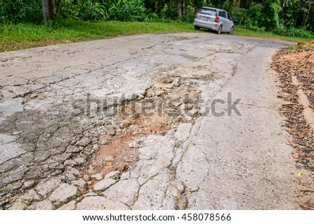 Gravel on the dirt road, which cracks due to water erosion and land subsidence. - stock photo