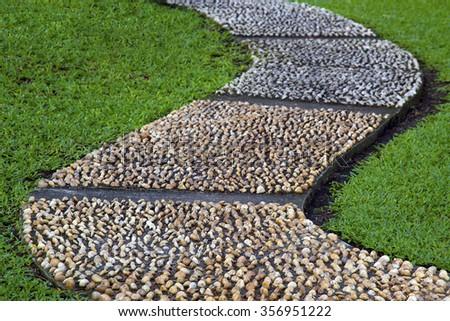 gravel pebble rock stone curvy pathway in the park garden - stock photo