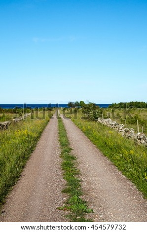Gravel road at the swedish island Oland straight to the coast of the Baltic Sea