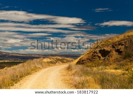 Gravel road in a country side in New Zealand - stock photo