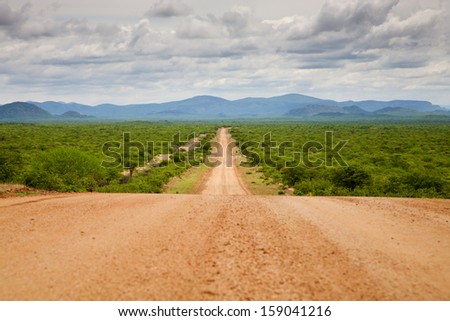 Gravel road in the north of Namibia with the Zebra Mountains in the background - stock photo