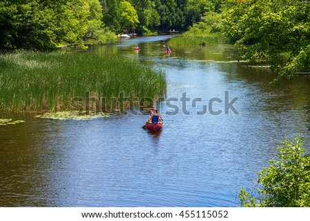 Gravenhurst, Ontario - July 17, 2016: Two male canoeists and a pair of kayakers paddling on a small placid stream near Lake Muskoka.