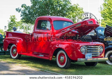 Gravenhurst, Ontario - June 18, 2016: Red vintage Ford truck with white-rim tires and an open hood  - stock photo
