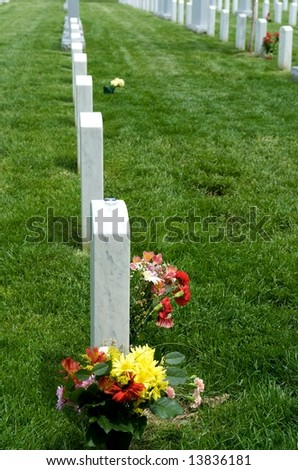 Graves and gravestones with flowers at Arlington National Cemetery - stock photo