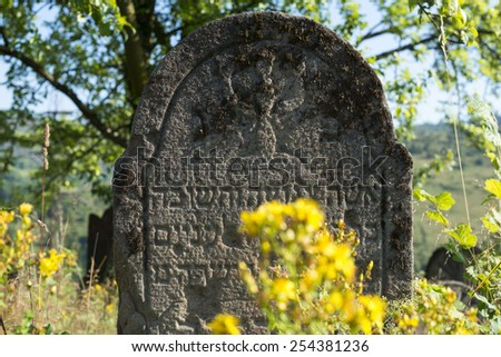 Gravestone in the old abandoned Jewish cemetery in the Ukrainian Carpathian Mountains. - stock photo