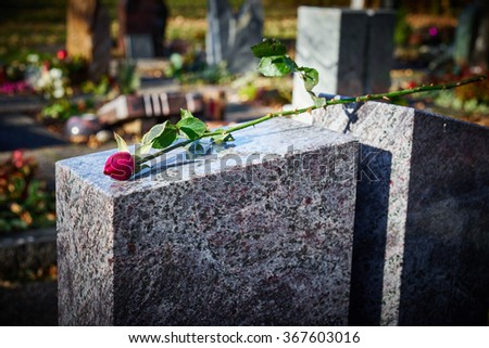 Gravestone with withered rose / Tombstone on graveyard / Sorrow about loss of beloved ones - stock photo