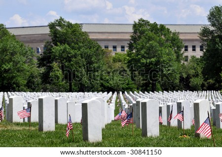 Gravestones decorated with U.S. flags to commemorate Memorial Day at the Arlington National Cemetery in Arlington, Virginia, near Washington DC, with Pentagon in the background. - stock photo