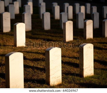 Gravestones lit by the setting sun in Arlington Cemetery - stock photo