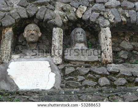 Gravestones with stone statues at the ancient Roman city of Pompeii, which was destroyed and buried during the eruption of Mount Vesuvius in 79 AD - stock photo