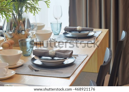 Gray and white tableware with jar of flower in dining room