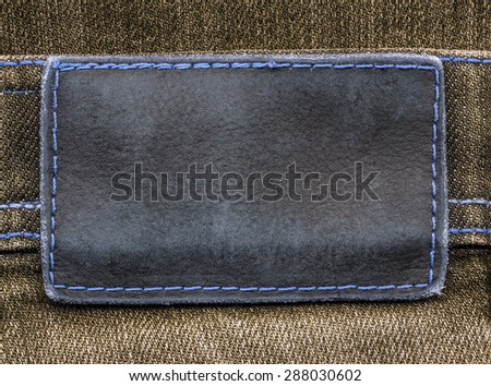gray-blue leather label on brown  jeans background