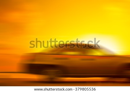 gray car in motion blur on the road towards the setting sun - stock photo