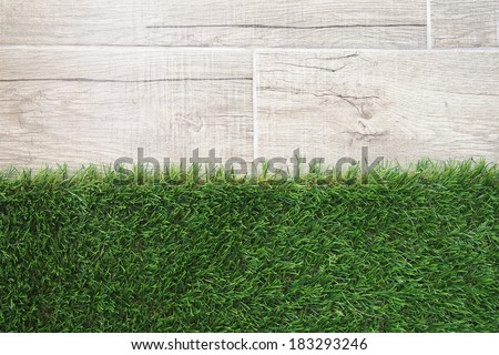 gray ceramic tiles and green artificial grass - top view - stock photo