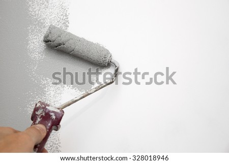 gray color painting wall with roller in hand - stock photo