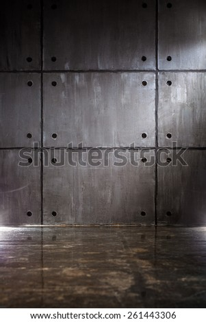 Gray concrete wall with big blocks and floor with reflection - stock photo