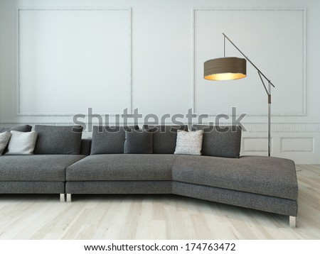 Gray couch and floor lamp against white wall - stock photo