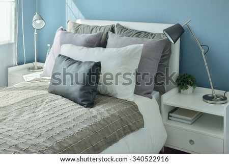Gray, dark gray and beige pillows on bed with blue wall bedroom - stock photo