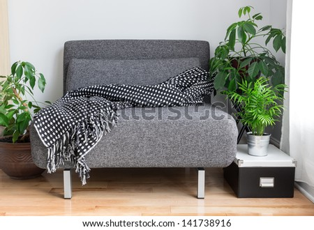 Gray fabric chair with cozy throw, and green plants in the living room. - stock photo