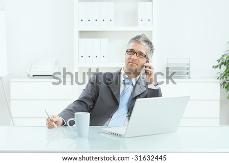 Gray haired executive businessman working on laptop computer at desk, in office, calling on mobile phone.