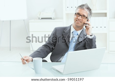 Gray haired executive businessman working on laptop computer at desk, in office, calling on mobile phone. - stock photo