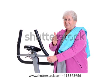 gray-haired female senior with thumb up train with fitness machine - stock photo