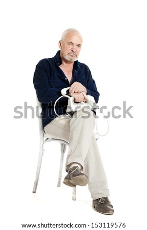 Gray-haired man sitting on a chair and holding electric iron on white background