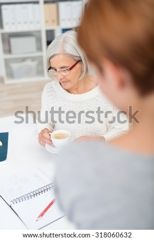 Gray-Haired Senior Businesswoman Reviewing Some Documents on the Table While Having a Cup of Coffee - stock photo