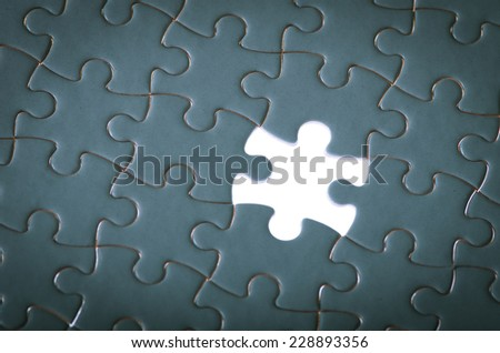 gray jigsaw puzzle with missing piece light glow concept of searching solution for a problem - stock photo