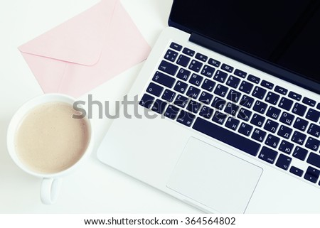 gray laptop computer on white table with a cup of coffee and a pink envelope breakfast business freelance fashion keyboard office - stock photo