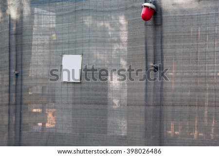 gray mesh fence with red lantern on a building site - stock photo