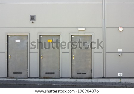 Gray metal wall and three armor doors. Small video camera over an entrance - stock photo