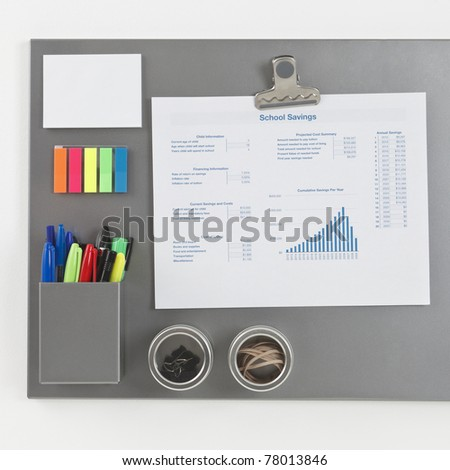 Gray metallic magnetic board with a spreadsheet printout held by a magnetic clip - stock photo