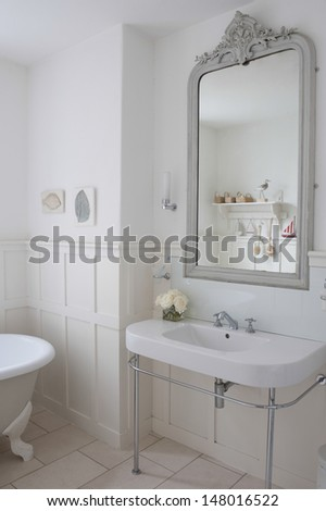 Gray painter mirror above bathroom sink