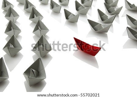 gray paper boats sailing in one direction, red boat to the other, isolated on white - stock photo