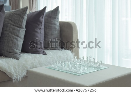 Gray pillows on sofa with crystal chess in the center low table - stock photo