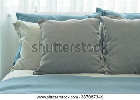 gray pillows setting on blue color scheme bedding