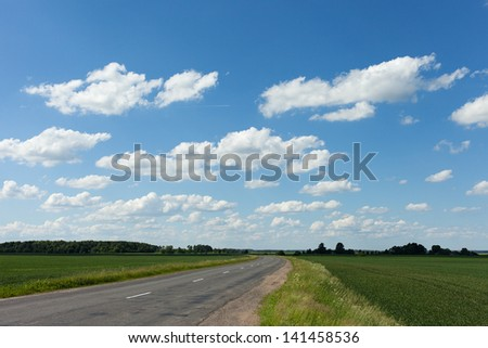 Gray road in green field.