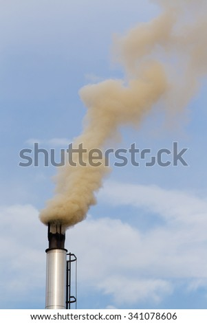 Gray smoke from chimney against blue sky with white clouds - stock photo